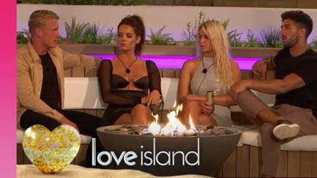 Love Island contestants sit around near a fire.
