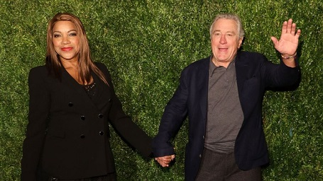 Robert De Niro and Grace Hightower attending an event with a grassy background.