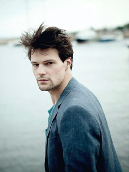 Danila posing for a photo by the river.