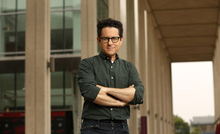 J.J. Abrams posing with his hands folded under 20 feet tall beams.
