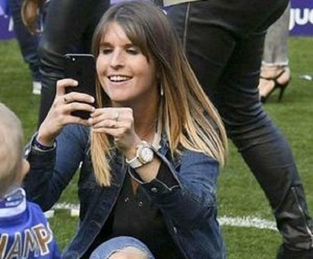 Natacha Van Honacker on the pitch taking pictures of her children and husband.