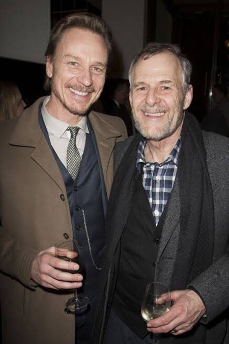 Ian Gelder and Ben Daniels hugging and drinking together.