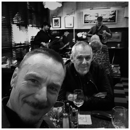 Ian Gelder and Ben Daniels inside a restaurant sharing wine.