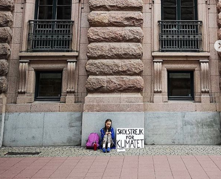 Greta sitting on the floor outside a building with placard beside her.