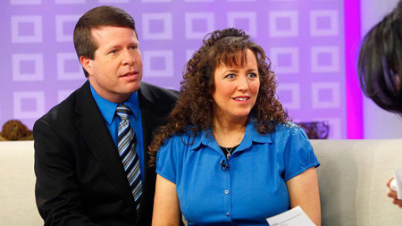 Jim Bob and Michelle Duggar sitting on a couch.