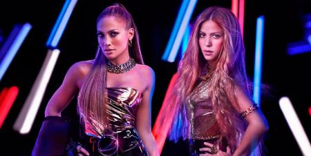 Jennifer Lopez and Shakira posing wearing shiny dresses and blue and red color lights in the background.
