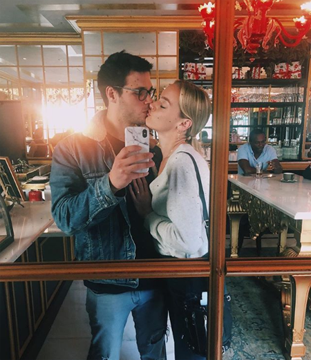 Rachel Skarsten and Alexandre Robicquet taking a selfie while kissing in a coffee shop.