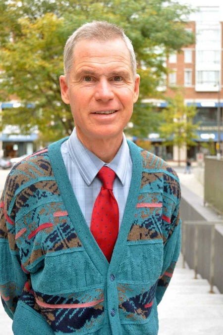 John Rodden wearing a sweater outside a shirt and a tie, posing with his hands back.