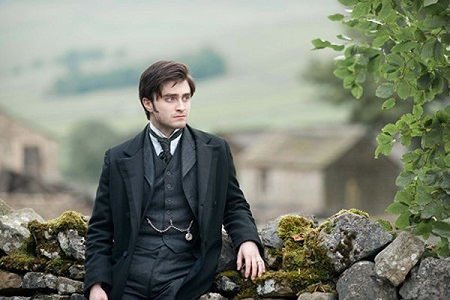 Daniel Radcliffe posing on a stone wall wearing a suit and looking sideways from the camera.