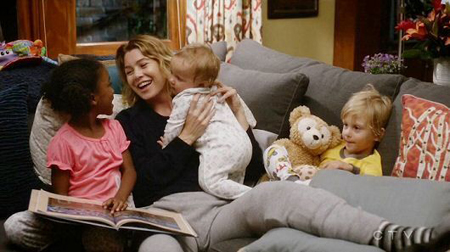 Meredith Grey with all of her children siting on a couch.