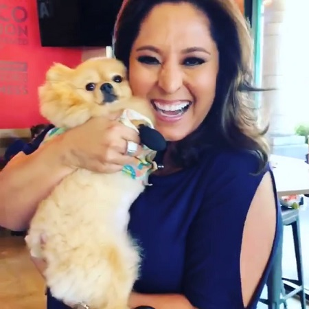 The Beautiful Lynette Romero smiling while holding a dog hugging her face.