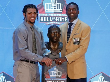 Former NFL wide receiver Randy Moss (right) poses with a bust of himself and with his presenter, son Thaddeus Moss during the inductions at the Pro Football Hall of Fame in August 2018 in Canton, Ohio.