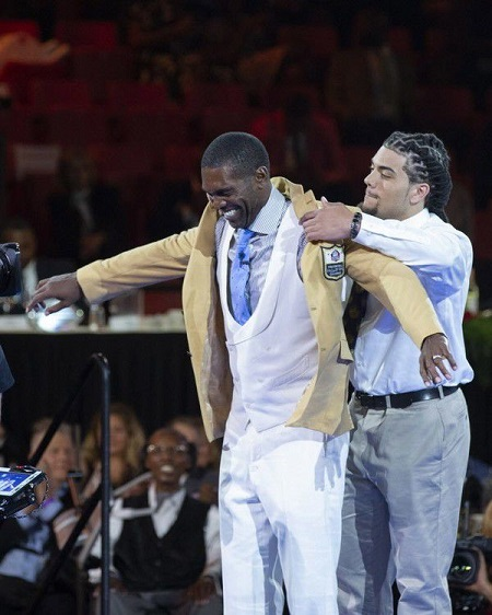 Randy Moss receives his Pro Football Hall of Fame gold jacket from his son and LSU tight-end Thaddeus Moss during the Hall of Fame Gold Jacket dinner on August 3, 2018.