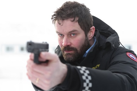 Björn Hlynur Haraldsson in the movie 'Fortitude' pointing a gun at someone.