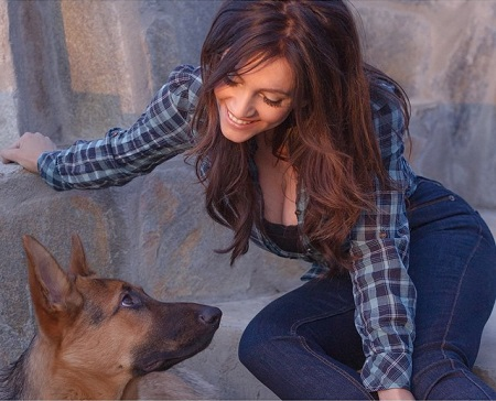 Denise Milani giving a smile to her dog, Lukita, looking down on him.