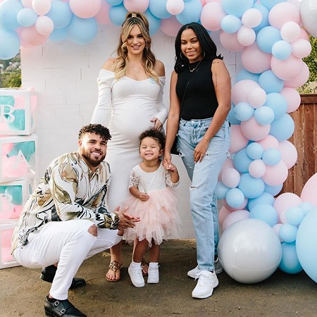 Cory Wharton sitting in his daughter's height who is smiling hardly, as Taylor stands with her hand in her belly besides Cheyenne Floyd.