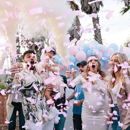 Taylor Selfridge gasing with surprise as pin confetti flies out of their launch poles with Cory Wharton also looking shocked while holding Ryder.