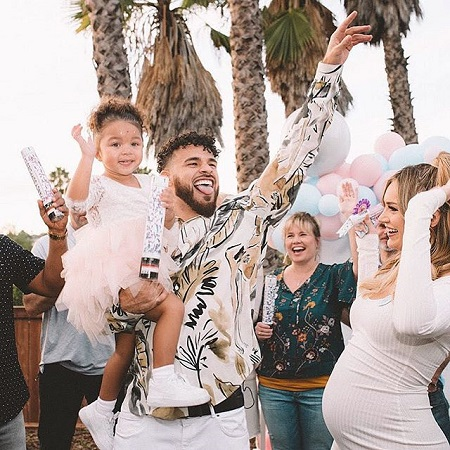 Cory Wharton holding daughter Ryder K with pregnant Taylor Selfridge at their Baby's Gender Reveal Party.