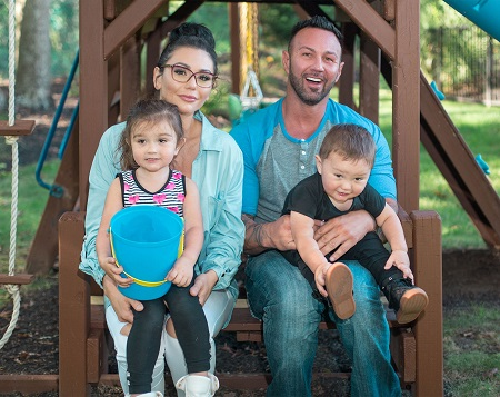 JWoww and Roger Mathews with their two kids in a playground ferris wheel.