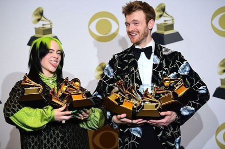 Billie Eilish sticking her tongue out with O'Connell, both holding the Grammys they won.