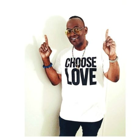 "Randy Jackson with his index fingers pointed upwards while wearing a white T-shirt that read, ""CHOOSE LOVE""."