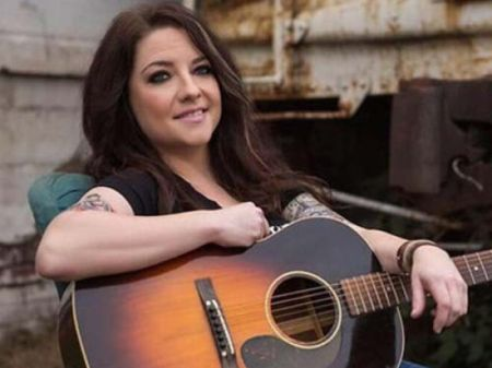 Ashley McBryde poses a picture with a guitar in her hand.