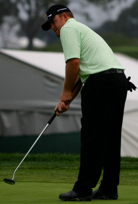 JB Holmes in a green t-shirt playing golf.