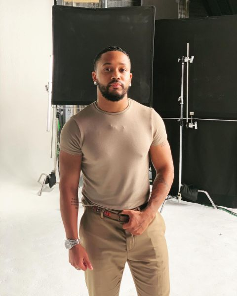 Romeo Miller poses a picture in a brown t-shirt.