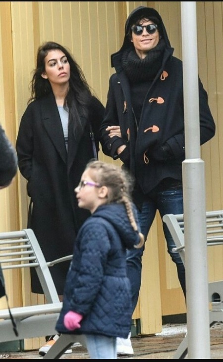 Cristiano Ronaldo in his disguise and smiling while walking with girlfriend Georgina Rodriguez during the date to Disneyland.