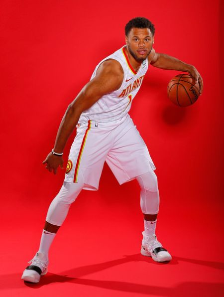 Justin Anderson holding a basketball for a photoshoot with red background.
