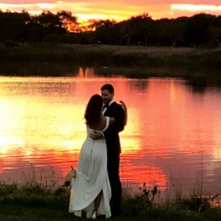 Sawyer Spielberg and Raye Levine at sunset beside a lake after their wedding.