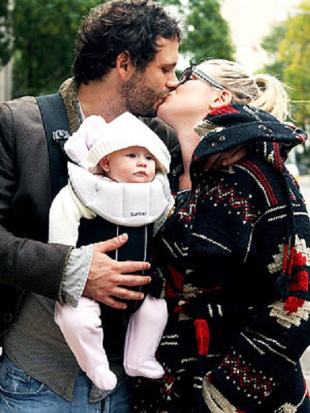 Jeremy Sisto kissing wife Addie Lane while holding their daughter in a carry-on.