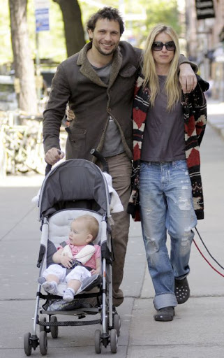 Jeremy Sisto with his arm around wife Addie Lane as he pushes the stroller carrying their daughter with his other hand.