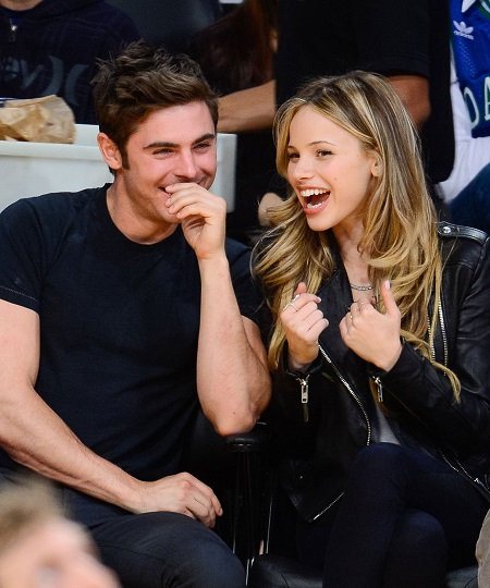 Zac Efron and Halston Sage laugh up as they attend a basketball match in April 2014.