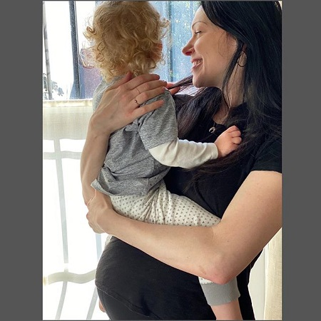 Laura Prepon holding Ella in her arms and revealing the growing baby bump.