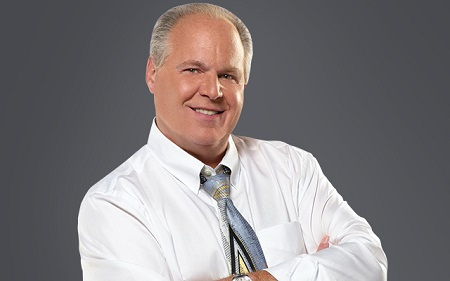 Rush Limbaugh in white shirt folding hands with a smile.
