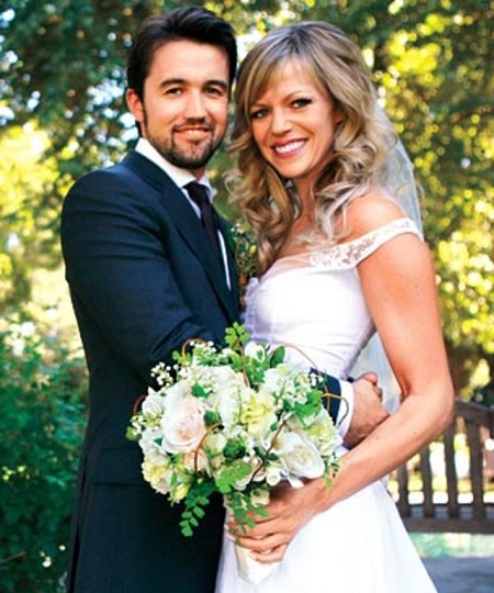 Rob McElhenney putting his arms around his wife Kaitlin Olson in their wedding dresses.