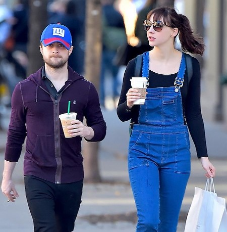 erin darke daniel radcliffe walking on the street with shopping bags on their hands.