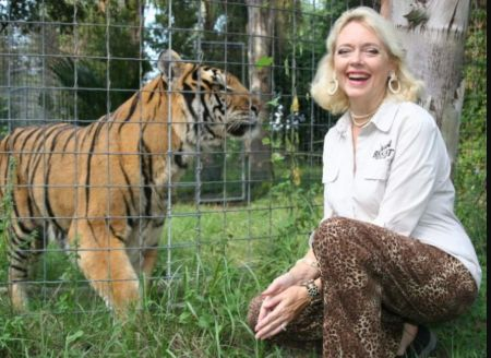 Carole Baskin Net Worth: Carole Baskin in a white t-shirt poses with a tiger.