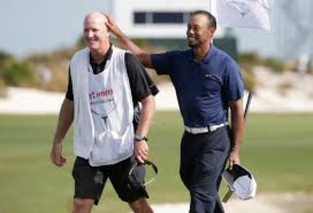 Tiger Woods in dark blue pats the head of Joe LaCava.