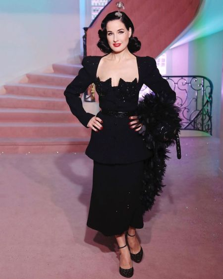 Dita Von Teese in a black dress poses for a picture.