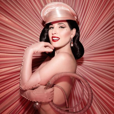Dita Von Teese in a designer costume poses for a photoshoot.