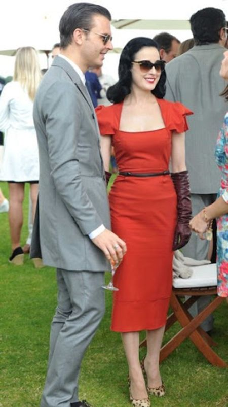 Theo Hutchcraft in a grey suit poses a picture with model Dita Von Teese.