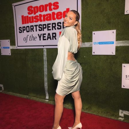 Camille Kostek Net Worth: Camille Kostek in a white dress poses at the Sports Illustrated event.