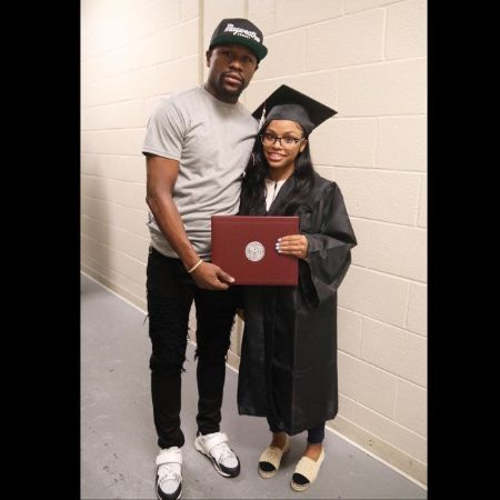 Iyanna Mayweather in her graduation gown poses a picture with Floyd Mayweather.