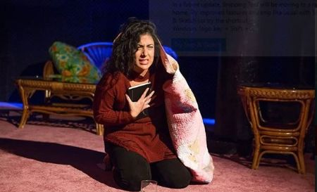 Nadine Malouf in a red top acting during a stage show.