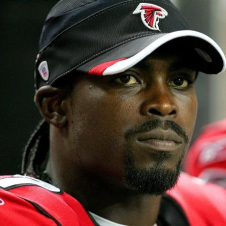 Michael Vick in a red jacket and black cap caught at the camera.