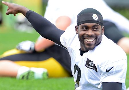 Michael Vick in a white t-shirt and black hat shows something to his friend.