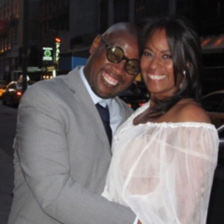 Wendy Credle in a white dress poses a picture with Andre Harrell.