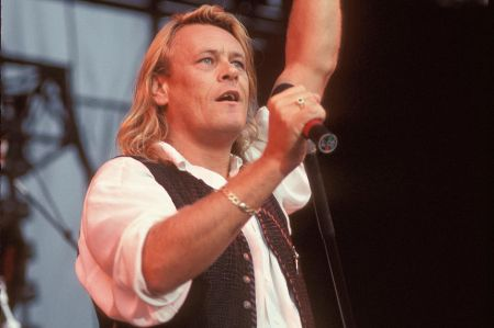 Brian Howe singing at a concert.